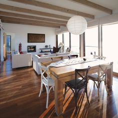 Light floods the living and dining rooms, meaning Schneider rarely needs to turn on a lamp during the day. Fake Beam, Hardwood Floors, Flooring, Floor Ceiling, Facade House, Dining Table, Dining Rooms, Architecture Design, Indoor