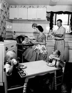 Vintage Kitchen mother feeds a baby seated in a high chair while the father dries his hands and smiles at their son and daughter, who are eating at a small table in a kitchen. Vintage Pictures, Old Pictures, Vintage Images, Old Photos, Vintage Family Photos, Antique Photos, Photo Vintage, Vintage Love, Vintage Ads