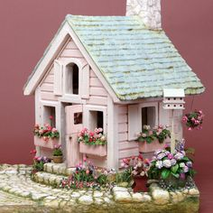 The Pink Playhouse, by Polly Morris, 1996. Construction secrets: structure and landscaping all made from foam core, mat board & card stock. Joint compound was used to good effect to create slate roof, wooden siding, stone fireplace & chimney, cobblestones & stepping stones. Sand, heavily sprinkled between the stones, looks like moss once painted.