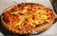 Southern Tomato Pie (adapted from pauladean.com)    Serves 6 to 8        4 large tomatoes, peeled* and sliced 1/4″ thick      10 fresh basil leaves, chopped      1/2 cup green onions, chopped      1 pre-baked 9″ deep dish pie crust      1 cup grated mozzarella cheese      1 cup grated cheddar cheese      1/4 cup mayonnaise      salt and pepper