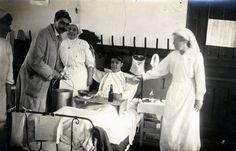 Soldat blessé sur un lit d'hôpital, entouré de médecin et d'infirmières, période 1914-1918