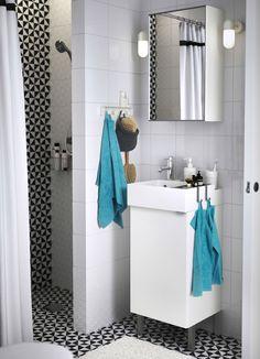 Baño con lavabo blanco, un espejo y toallas turquesa.