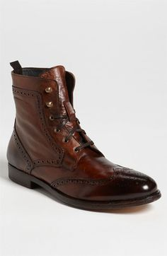 An antiqued patina and weathered construction define a classic boot styled with meticulous wingtip broguing.