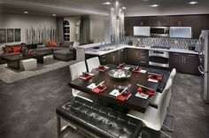 Steel, gray and black with red accents create a stunning contemporary kitchen, eating area and great room. Residence 1 by Brookfield Homes. Carlsbad, CA.