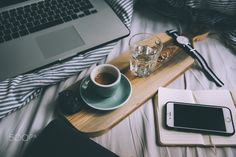 Morning working in bed essentials: laptop, smartphone,fresh coffee
