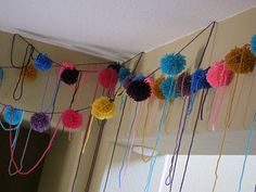 """What would a kitty cat party be without yarn? I couldn't get enough of these cute and colorful handmade poms. I strung them everywhere I could. It was a great way to bring in color to the party. I assure you that our cats had a great time """"helping"""" me hang these!"""