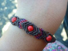 I made this bracelet with a lof of LOVE. It´s made out of waxed polyester cord in the colour chocolate brown with red and purple highlights. I also used three red coral beads for it. You can easily adjust the bracelet with a sliding knot. Feel free to ask me questions via message :-) P.S. My jewelery is handmade, unique and not produced by a machine.