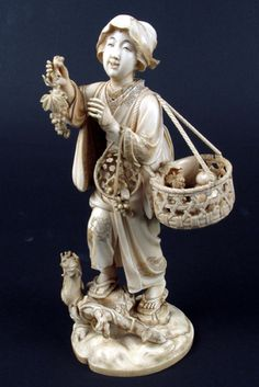 MEIJI PERIOD JAPANESE IVORY CARVED FIGURE, depicting woman vendor hawking her wares of fruit with large basket suspended from her shoulder, smaller basket on her arm, standing on tree stumps on attached plinth. Height 9 1/4 in., signed within a red rectangle underfoot together with incised flower stalk.