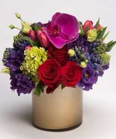 Sugar Plum This colorful winter collection of reds, blues, lavenders and greens - including roses, orchids, hyacinth and tulips - is designed in a gold cylinder vase,