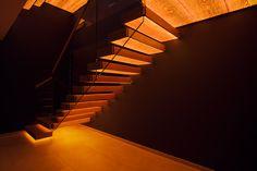 Jede Treppenstufe leuchtet auf der Unterseite durch das echte Eichenholzfurnier. Da zudem die Glasgeländer quasi unsichtbar sind, entsteht ein Rhythmus aus Licht, das durch die Holzmaserung zudem sehr wohnlich warm wirkt. Die Maserung lässt das Licht in der Fläche lebendig erscheinen und weckt Assoziationen zum Licht eines Sonnenuntergangs. Im Gesamtbild wirkt die Treppe gemeinsam mit den großen Gebäudeöffnungen sehr skulptural und eindrucksvoll. Stairs, Home Decor, Stair Treads, Hand Railing, Wood Grain, Stairway, Decoration Home, Room Decor, Staircases