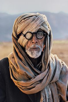 politics-war:    Afghan Refugee, Pakistan.   Photo: Steve McCurry. Man, male, face, glasses, scarf, a bit funny, culture, beard, oldie, wrinckled, photograph, photo
