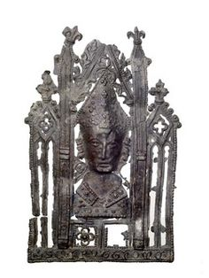 Pilgrim badge from the shrine of St Thomas Becket at Canterbury Cathedral. This badge depicts the mitred head-shaped reliquary bust that held the remains of Becket's skull. The bust is surrounded by an architectural frame. Archaeological and stylistic evidence suggests that this type of badge was first made around the time of the shrine's third jubilee, in 1320. Along the base is an inscription: '+ S CAPVT THOME' (meaning 'Saint Thomas's head').