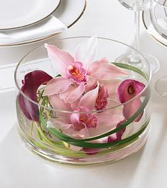 lavender cymbidium orchids and three mini calla lilies float in a clear glass candleholde