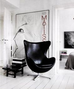 Black leather egg chair, huge leaning print, black gloss table.