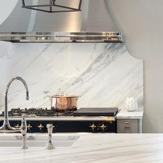 shiny vent hood, white backsplash White and gray kitchen features light gray cabinets paired with calacatta marble…