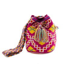 This beautiful drawstring mochila bag is made entirely by hand by a woman of the Wayuu community from the northern territory of Colombia. It is