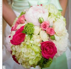 bouquet of ivory peonies, light green hydrangeas, ivory and dark pink–edged Rossini roses, green viburnum, and pink spray roses.