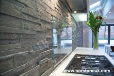 Natural Stacked Stone Backsplash made with Norstone series Charcoal Ledgestone panel system with frosted glass guard near stove tops Stacked Stone Backsplash, Natural Stone Backsplash, Stacked Stone Walls, Stone Tiles, Stacked Stones, Stove Backsplash, Mirror Backsplash, Backsplash Ideas, Stone Cladding