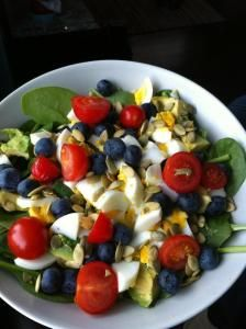 Breakfast salad: baby spinach, cucumber, avocado, tomatoes, chopped hard boiled eggs, blueberries and raw pepitas.