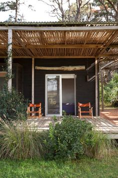 Rising from the grass, shaded by a stand of trees is a simple beach house celebrating its surro...
