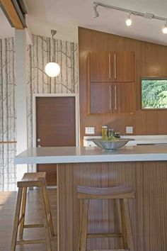 There are so many things to love - the wallpaper, the phenomenal veneer, the bar stools, the hardware on the cabinets ...