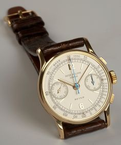 Elegant men's watch with a beige face and blue second hand.