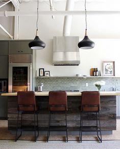Modern kitchen with black pendant lights, green backsplash, and leather barstools