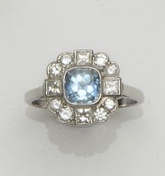 An aquamarine and diamond dress ring  The square cushion-shaped fancy-cut aquamarine collet set within a surround of brilliant-cut diamonds, with millegrain set princess-cut diamonds to the cardinal points, shank stamped '18ct',