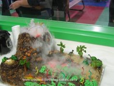 Dry ice, hot water, colored marshmallow fluff. Erupting volcano cake! Wow!