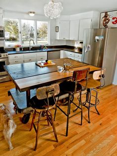 Everything about this kitchen speaks to me.  Light, bright, airy, wooden floor, quirky furniture and lighting... and of course the dog!