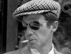 """Jean-Paul Belmondo , with Ray-ban sunglasses and a """"grandfather """" cap, in Breathless ( A bout de souffle ) by Jean-Luc Godard"""