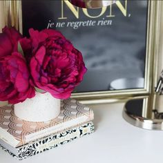 The French Bedroom Company Blog | How To: Make Your Home Insta-Worthy. Get your home instagram ready with our top tips and ideas. We love this close up of Apartment 4 interior blogs vignette with black and gold print with gold lamp and dark red flowers. Stack of books always make a great display