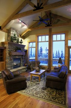 Here's another rustic styled living room, richly appointed with dark leather seating over a floral rug on hardwood flooring. Stone fireplace with large mantle stands next to full height windows.