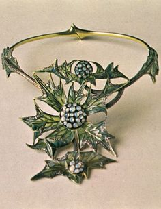 Lucien Gaillard - An Art Nouveau Thistle necklet, 1903-04. Consisting of two rigid semicircles with a spring-hinge at centre back; the thistle-like composition is executed in grey-green opaque and plique-à-jour enamels for the leaves, and light translucent brown for the stems. Three clusters of buds are set with opals, and the edges of the leaves are picked out in diamonds. Source: From Slave to Siren: Dora Jane Janson. #Gaillard #ArtNouveau #necklace