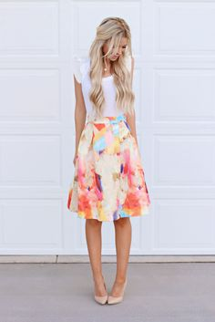 Long flared skirts are flattering and timeless. Wear one with a white tee and nude heels for an airy spring look.
