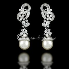 CZ and pearl bridal earrings with so much lovely detail you con't help but say wow! A single off-white pearl is captured by a cap of baguette CZ hanging from a