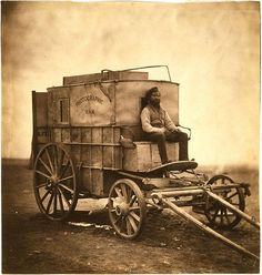 Roger Fenton's assistant seated on Fenton's photographic van, Crimea, 1855