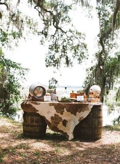Rustic chic wedding cocktail hour bar idea - two wine barrels + cowhide table runner {Kelli Boyd Photography}
