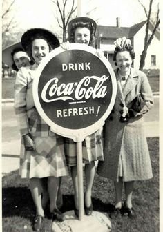 Vintage photo of ladies standing by 'Drink Coca~Cola Refresh!' sign. Hartford, Wisconsin 1939