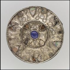 Disk Brooch.  Date: 7th century CE. Culture: Frankish. Medium: Silver-gilt, glass, pearl, Gilded silver with filigree and glass inlays. Dimensions: Overall: 1 5/8 x 9/16 in. (4.1 x 1.5 cm). Classification: Metalwork-Silver. Credit Line: Gift of J. Pierpont Morgan, 1917 Accession Number: 17.193.10.