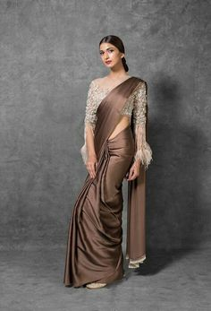 Brown and White Silk Saree features Pure Silk Satin Saree and a Tulle Blouse. Embroidery work is hand-crafted using thread, stone embellishments and sequence. For customers that require Modest Tailoring, please state it in the tailoring form in th Trendy Sarees, Stylish Sarees, Simple Sarees, Fancy Sarees, Simple Saree Designs, Saree Blouse Patterns, Saree Blouse Designs, New Saree Designs, Dress Indian Style