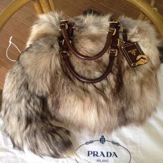 Prada Brown Fox Fur Hobo Tote Large AMAZINGGGG absolutely stunning fox fur prada bag in excellent condition! Purchased from Portero a number of years ago, comes with authenticity card pictured. Gorgeous shades of brown, fur all over, leather handles with gold accents, fox fur tail attachment. Other than a bit of vintage fur smell, bag is in excellent pre owned condition. Fur is thick and lush! Selling for a friend, no trades on this item. Prada Bags Hobos