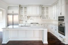 Stunning kitchen features glazed white cabinets adorned with oil-rubbed bronze hardware alongside white quartzite countertops and a linear tiled backsplash.
