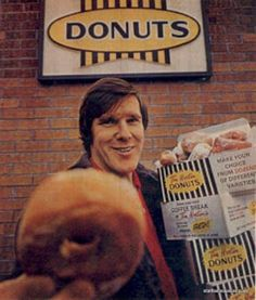 Former Maple Leaf defenceman Tim Horton offering you a donut, outside one of his coffee shops he first opened in when he was still playing. There are now Tim Hortons across Canada.