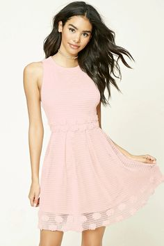 An open-knit dress featuring floral appliques at the waist and hem, scoop neck, sleeveless cut, a pleated skirt, and an exposed back zipper.