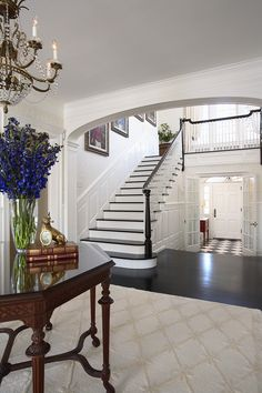 Design Studio│ Greeted by a black and white harlequin floor pattern, this traditional foyer reflects the style of this restored 1920's home, with wainscoting and a neutral paint palate.