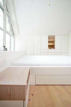 V této podkrovní ložnici bylo třeba vše přizpůsobit tvaru skosených stěn, aby se mohl celý prostor co nejefektivněji využít. Šikmé tvary se tak staly hlavním designovým prvkem celého projektu. Naprostou většinu nábytku tvoří bílé lamino pečlivě lemující okraje zdí a stropu. Úložné prostory jsou pak precizně zasazeny těsně vedle sebe. Tvoří nádherný jednolitý celek, který je narušen jen tehdy, když některá dvířka otevřete. Také postel je tvarována do jednoho bloku. Floating Nightstand, Bench, Storage, Table, Furniture, Home Decor, Floating Headboard, Purse Storage, Decoration Home