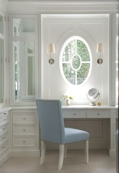 Elegant walk-in closet with an oval window illuminated by Visual Comfort Lighting Thomas O'Brien Bryant Sconces in Polished nickel over a white vanity with marble top paired with a blue nailhead chair flanked by mirrored cabinets. Walking Closet, Bedroom Window Dressing, Dressing Rooms, Built In Dressing Table, Dressing Tables, Built In Vanity, Closet Vanity, Visual Comfort Lighting, Desk With Drawers