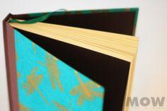 Libélulas Doradas....! Cuaderno MOW 100 hojas papel ahuesado, tapa forrada en papel de libélulas doradas en relieve, vinilo color café con pequeños destellos dorados. Hoja de guarda color café moro, cinta separadora color verde.