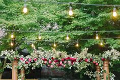 These beautiful café lights over our custom built pergola! All dressed up with greenery and flowers for a perfect wedding focal point!